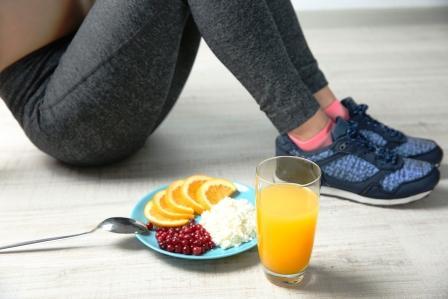 Žena drží zónovú diétu, sedí a podlahe a vedľa seba má zdravé raňajky