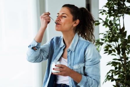 Mladá žena je biely jogurt a drží jogurtovú diétu