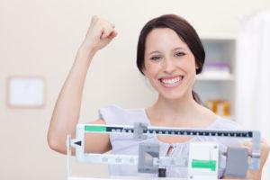 Usmiata žena sa váži na váhe