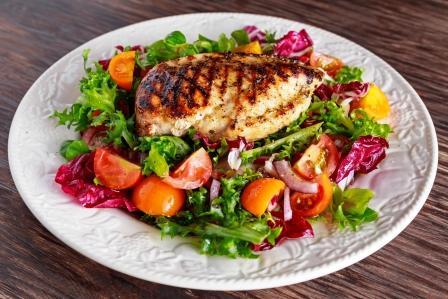 Delená strava na tanieri - grilované kuracie prsia s čerstvým zeleninovým šalátom - zdravé jedlo