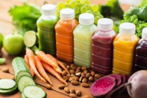 rôzne šťavy z ovocia a zeleniny na detoxikáciu tela, v popredí mandle a zelenina