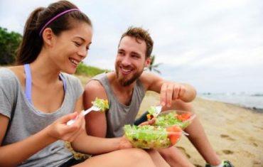 Ako zvládnuť diétu v lete - zena a muz jedia pri mori.jpg