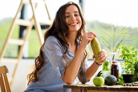 Krásna šťastná žena sedí s nápojmi a zdravé zelené jedlo a drží Dash dietu