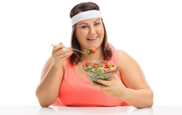 žena drží diétu, sedí pri stole a je šalát