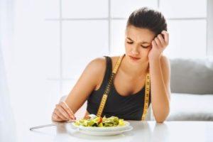 Mladá rozrušená žena sedí v kuchyni pred tanierom, meter okolo krku
